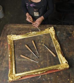 Artisan sculptant un cadre en bois doré à l'or fin